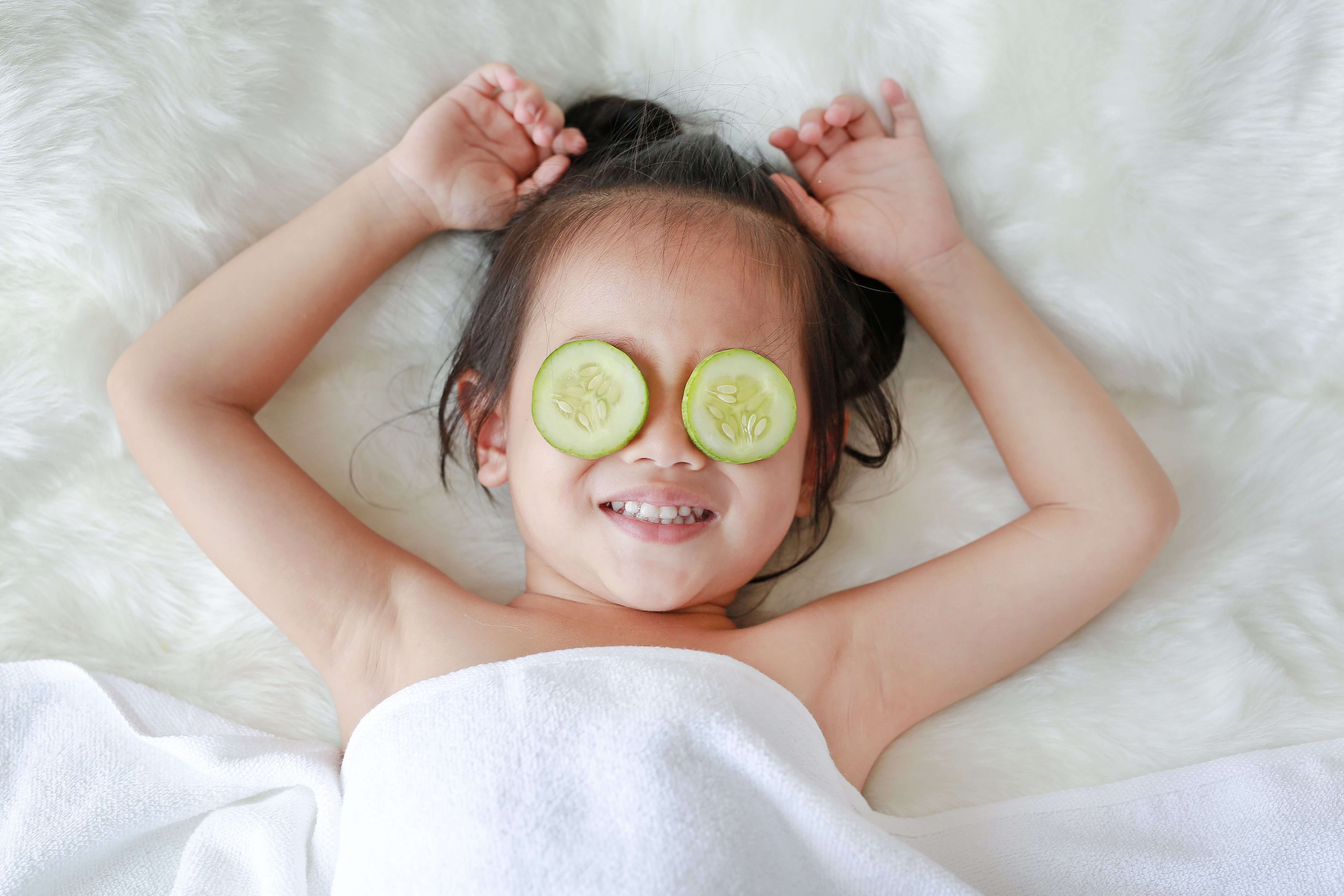 Baby with cucumber slices on eyes for rest and nourishment
